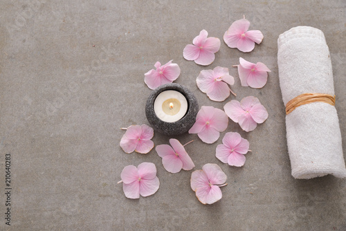Aluminium Spa Many Pink hydrangea petals with candle in stone bowl ,towel on gray background