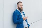 mann lehnt lässig an einer wand und hört musik mit seinem smartphone