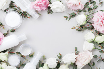 Frame from natural cosmetic and flowers on pastel table top view. Flat lay style. © juliasudnitskaya