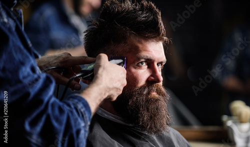 Hands of barber with hair clipper, close up. Hipster bearded client getting hairstyle. Barbershop concept. Barber works with hair clipper. Man with beard in hairdressers chair, dark background © Roman Stetsyk