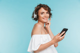 Portrait of a happy young woman listening to music - 210648439