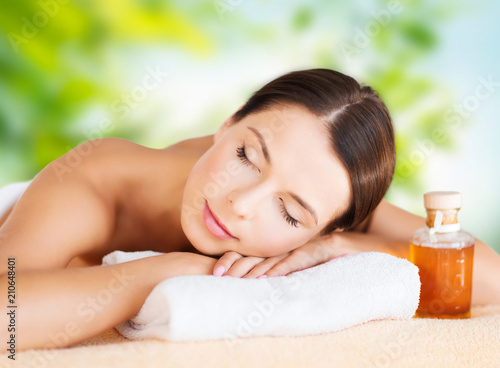 wellness, spa and beauty concept - close up of beautiful woman with bottle of massage or essential oil over green natural background © Syda Productions