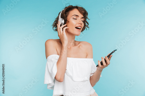 Portrait of a delighted young woman listening to music - 210648451