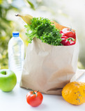 food, diet and healthy eating concept - paper bag with fresh fruits and vegetables and water bottle on table over green natural background