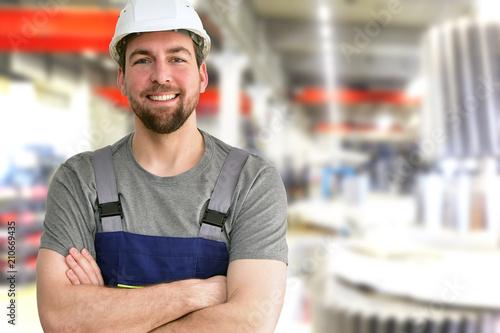 Leinwanddruck Bild closeup Portrait of a friendly workmen in mechanical engineering //  freundlicher Monteur im Maschinenbau - im hintergrund Fabrikhalle zur Herstellung von Getrieben