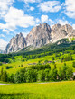 Leinwanddruck Bild - Rocky ridge of Pomagagnon Mountain above Cortina d'Ampezzo with green meadows and blue sky with white summer clouds, Dolomites,, Italy.