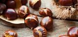 Roasted Sweet Chestnuts nuts on neutral wooden background closeup, macro, detail -  healthy seasonal snack. - 210672250