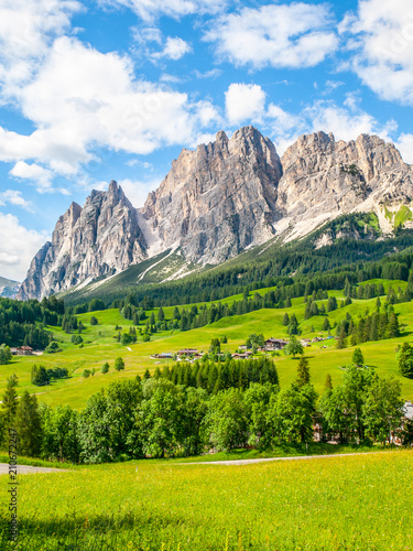 Leinwanddruck Bild Rocky ridge of Pomagagnon Mountain above Cortina d'Ampezzo with green meadows and blue sky with white summer clouds, Dolomites,, Italy.