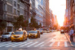Sunlight shines down a busy street in New York City with taxis stopped at the intersection