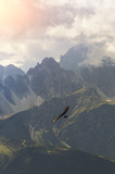 Hang glider high in the mountains. Extreme sport in the Alpine mountains - 210709435