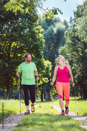Couple of man and woman doing Nordic Walking for sport