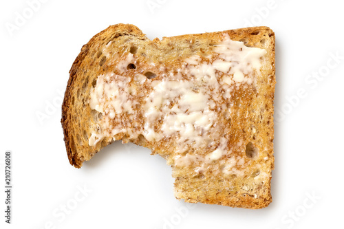 Masło plasterek grzanki z całej pszenicy na białym tle z góry. Ugryźć brakuje.