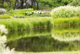 Beautiful pond in the garden. Water is reflecting the colorful grass and flowers and bushes. - 210728425
