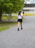 Caucasian woman jogging outdoors on a summer day wearing shorts and t-shirt. - 210730891