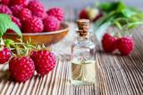A bottle of raspberry seed oil with fresh raspberries