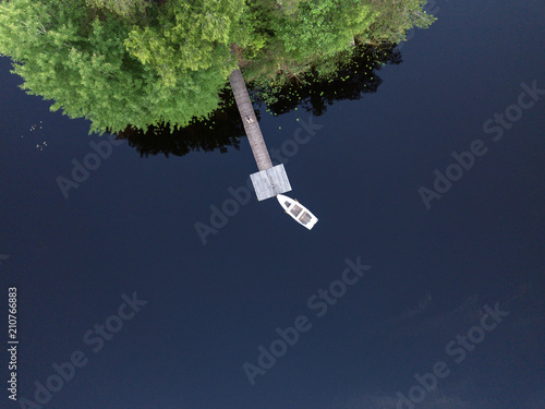 Aerial view of a wooden pier with an attached boat with reflecting clouds in the water, near a small green island  - 210766883