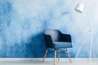 Leinwanddruck Bild - Modern dark blue chair and white metal lamp against ombre wall in a minimal style waiting room interior. Copy space. Real photo.