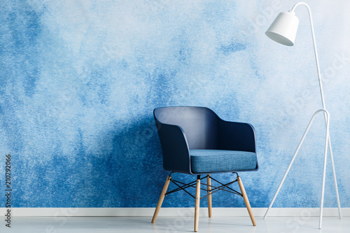 Leinwanddruck Bild Modern dark blue chair and white metal lamp against ombre wall in a minimal style waiting room interior. Copy space. Real photo.