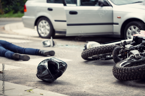 Black helmet and motorcycle after dangerous traffic incident with car on the street - 210794667
