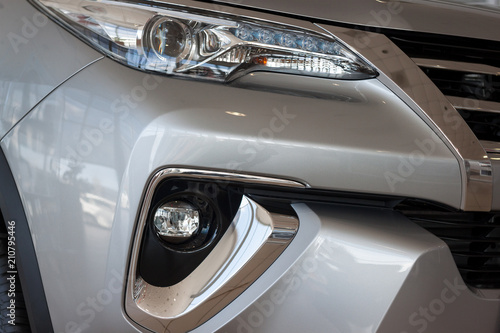 New vehicle with elegant head lamps in showroom. - 210795446