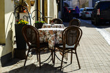 Street cafe or restaurant in the European city. Brown chairs and - 210800461