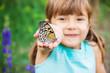 Leinwanddruck Bild - Child with a butterfly. Idea leuconoe. Selective focus.
