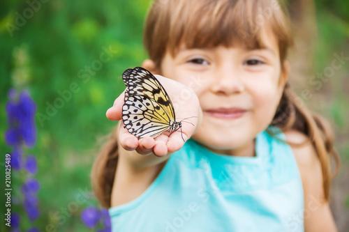 Leinwanddruck Bild Child with a butterfly. Idea leuconoe. Selective focus.