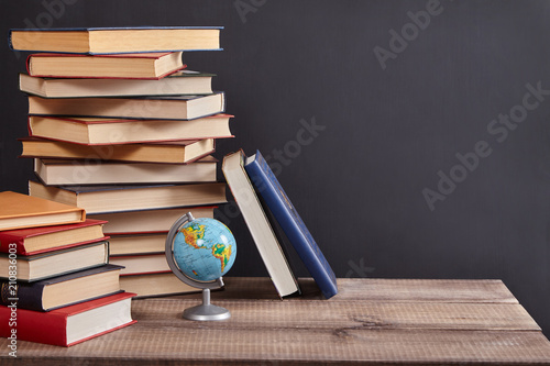 Fototapeta A pile of books with globe on the table. Blackboard background with copy space. Education concept.