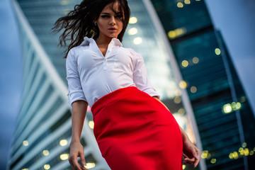 Brunette model wearing glasses, white shirt, red skirt, girl standing in business city
