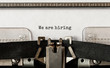 Text We are hiring typed on retro typewriter