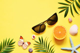 Tropical Background. Palm Trees Branches with starfish and seashell on yellow background. Travel. Copy space.