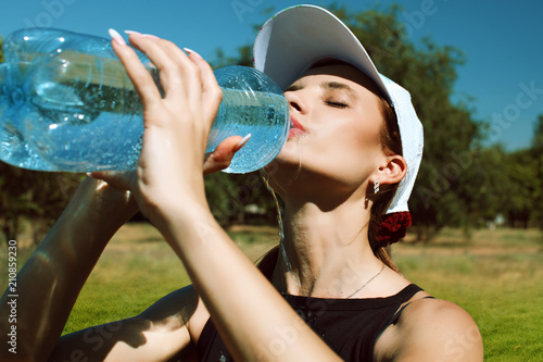 Aluminium Tennis Beautiful girl with a tennis racket against a background of nature drinking water