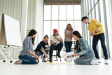 Young creative diverse group meeting and looking at project plan lay out on floor discuss or brainstorm business strategy with post note. Workshop for startup team in modern office. Happy workplace. - 210865039