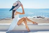 Frau sitzt in der Sonne an einem Strand in Griechenland