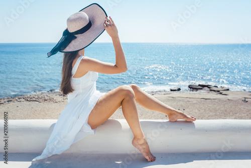 canvas print picture Frau sitzt in der Sonne an einem Strand in Griechenland