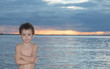 Adorable little boy playing with water at the sunset of river prairie in Palmas Tocantins, Brazil
