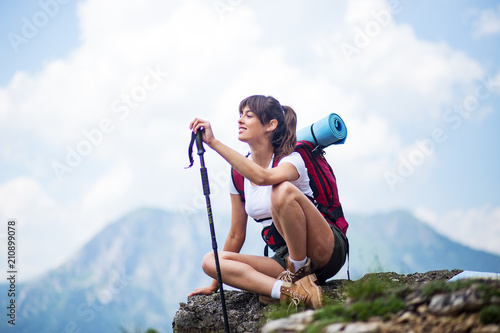Successful female hiker enjoy the view hiking on mountain peak - 210899078
