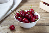 Cherries in the bowl on wooden table - 210902073