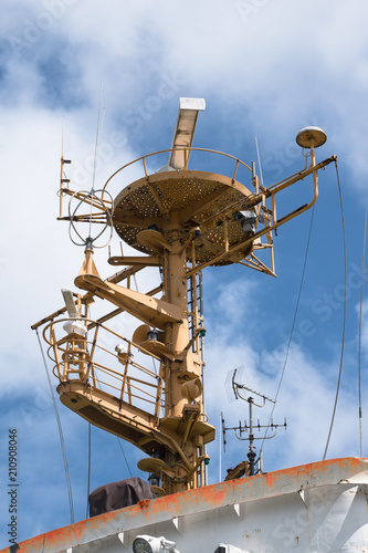 Aluminium Schip control tower with radar antenna and navigation equipment on an older industrial ship against the blue sky, vertical