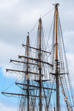 masts and rigging of a historic three-master sailing ship against the cloudy sky, travel and voyage concept, vertical - 210908412