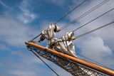 jib boom with reefed sails on the bow of a historic sailing ship against a blue sky with clouds, copy space - 210909004