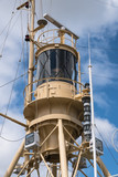 tower of a rescue ship with radar, lights and communication equipment against the blue sky with clouds, vertical - 210909099