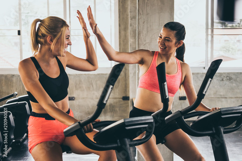 Wall mural Attractive young women working out together on exercise bike at the gym.