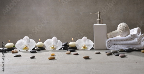 Aluminium Spa Three candle with pile of stones and white orchid , herbal ball.on towel ,oil on gray background