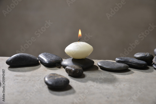 Aluminium Spa Candle with pile of black stones on gray background