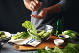 Man cooking green salad romaine lettuce healthy food - 210945013