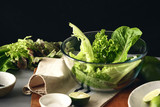 Large glass bowl green salad romaine lettuce black background Healthy food - 210945016