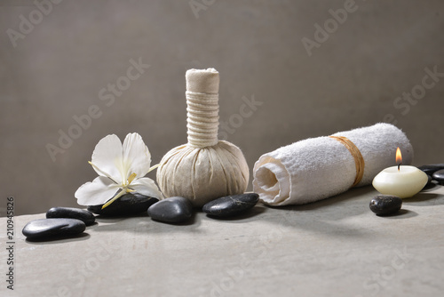 Aluminium Spa candle with pile of black stones and white orchid, herbal ball.towel on gray background