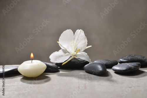 Aluminium Spa candle with pile of black stones and white orchid, on gray background