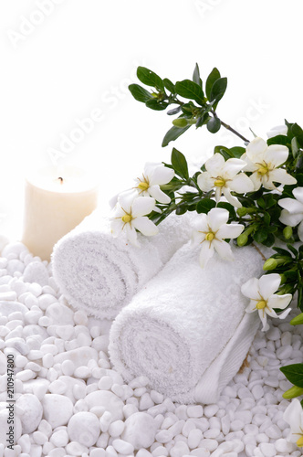 Aluminium Spa Rolled towel and candle and gardenia on white pebbles